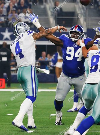 Dallas Cowboys quarterback Dak Prescott (4) throws as New York Giants defensive tackle Dalvin Tomlinson (94) attempts to block the pass during the first half of an NFL football game in Arlington, Texas