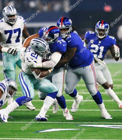 Dallas Cowboys running back Ezekiel Elliott (21) battles New York Giants defensive end Kerry Wynn (72) and defensive tackle John Jenkins (91) during the first half of an NFL football game in Arlington, Texas