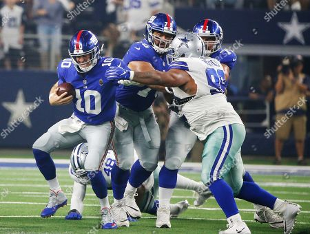 Dallas Cowboys nose tackle Antwaun Woods (99) pressures New York Giants quarterback Eli Manning (10) during the first half of an NFL football game in Arlington, Texas