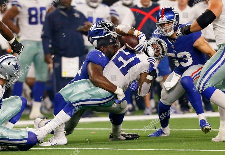 New York Giants defensive tackle Dalvin Tomlinson (94) loses his helmet as he hits Dallas Cowboys running back Ezekiel Elliott (21) during the first half of an NFL football game in Arlington, Texas