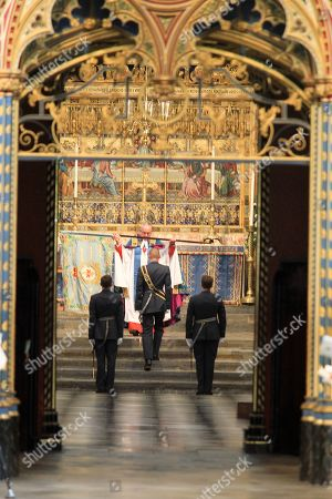 Stock Image of The Standard of the 92 Squadron of the Royal Air Force is returned by  The Dean of Westminster, The Very Reverend Dr John Hall, to the Standard Party at the end of the Service.