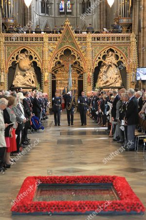 The Standard of the 92 Squadron of the Royal Air Force is returned by  The Dean of Westminster, The Very Reverend Dr John Hall, to the Standard Party at the end of the Service.