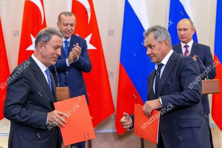 Russian Defense Minister Sergei Shoig (foreground R) and Turkish Defense Minister Hulusi Akar shake hands as Russian President Vladimir Putin (R)  and Turkish President Recep Tayyip Erdogan (2-L) look on during their joint news conference following the talks in the Bocharov Ruchei residence in the Black Sea resort of Sochi, Russia, Monday, 17 September 2018.  The presidents of Russia and Turkey are meeting in the Russian Black Sea resort of Sochi in a bid to find a diplomatic resolution to the crisis around Idlib, a rebel-held region in Syria.