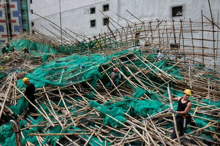 Workers remove bamboo scaffolding after it has collapsed, fell and blocked the street. Super Typhoon Mangkhut aftermath is visible in most districts of Hong Kong.