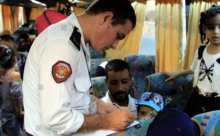Civil police check the identity of displaced Syrians upon their return from Lebanon to Damascus, Syria, on 17 September 2018. According to media reports, some 200 displaced Syrians arrived in Jdaidet Yabous and al-Dabbousyia crossings coming from Lebanon.  The reports said that the returnees will be transported to their villages and towns which were liberated by the Syrian army after cleaning their areas from militants.
