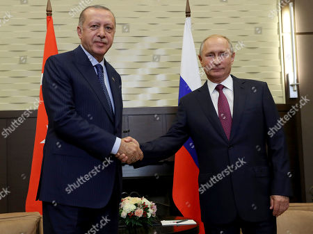 Russian President Vladimir Putin, right, shakes hands with Turkey's President Recep Tayyip Erdogan, left, prior to their meeting at the Bocharovy Ruchei residence, in Sochi, Russia, . The presidents met in the Russian Black Sea resort in a bid to find a diplomatic resolution to the crisis around a rebel-held region in Syria