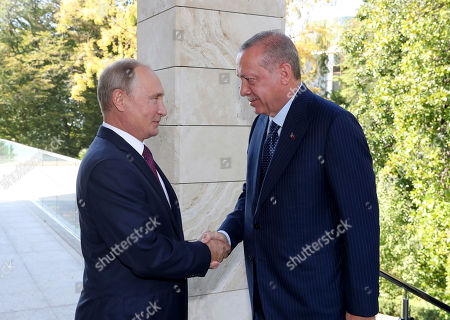 Russian President Vladimir Putin, left, welcomes Turkey's President Recep Tayyip Erdogan, right, prior to their meeting at the Bocharovy Ruchei residence, in Sochi, Russia, . The presidents met in the Russian Black Sea resort in a bid to find a diplomatic resolution to the crisis around a rebel-held region in Syria