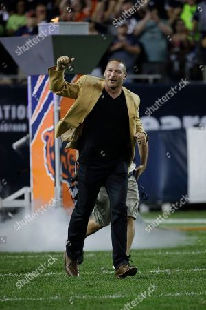 Former Chicago Bears and Hall of Fame linebacker Brian Urlacher runs to the field for a halftime ceremony to honor his induction into the Pro Football Hall of Fame during an NFL football game between Seattle Seahawks and Chicago Bears, in Chicago