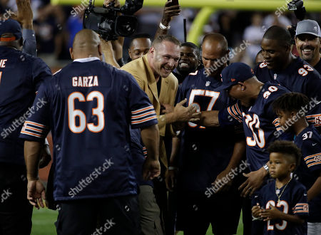Former Chicago Bears and Hall of Fame linebacker Brian Urlacher gets with former teammates before a halftime ceremony to honor his induction into the Pro Football Hall of Fame during an NFL football game between Seattle Seahawks and Chicago Bears, in Chicago