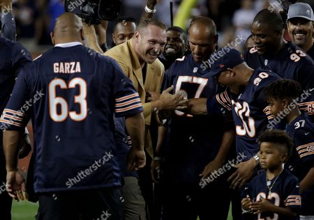 Former Chicago Bears and Hall of Fame linebacker Brian Urlacher celebrates during ra Ring of Excellence ceremony by the Bears during the halftime of an NFL football game, in Chicago