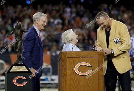 Chicago Bears chairman George McCaskey and owner Virginia Halas McCaskey celebrate with former Chicago Bears and Hall of Fame linebacker Brian Urlacher during a Ring of Excellence ceremony by the Bears during the halftime of an NFL football game against the Seattle Seahawks, in Chicago