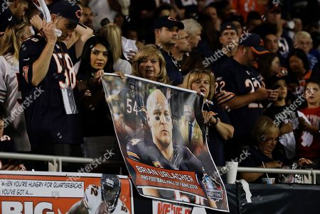 Fans cheer as former Chicago Bears and Hall of Fame linebacker Brian Urlacher speaks during a Ring of Excellence ceremony by the Bears during the halftime of an NFL football game against the Seattle Seahawks, in Chicago