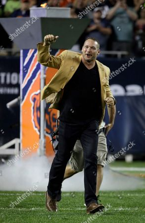 Former Chicago Bears and Hall of Fame linebacker Brian Urlacher runs to the field for a Ring of Excellence ceremony by the Bears during the halftime of an NFL football game, in Chicago