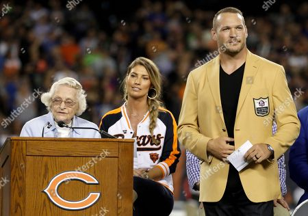 Chicago Bears owner Virginia Halas McCaskey, left, speaks as former Chicago Bears and Hall of Fame linebacker Brian Urlacher listens during a Ring of Excellence ceremony by the Bears during the halftime of an NFL football game, in Chicago