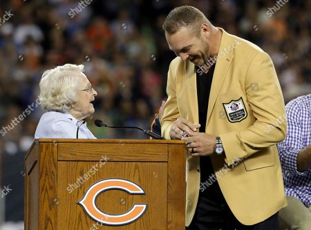 Former Chicago Bears and Hall of Fame linebacker Brian Urlacher receives a Ring of Excellence from Chicago Bears owner Virginia Halas McCaskey during the halftime of an NFL football game, in Chicago