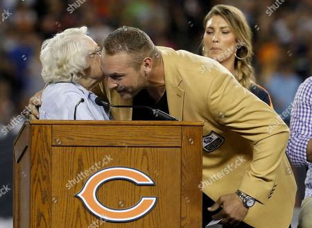 Former Chicago Bears and Hall of Fame linebacker Brian Urlacher hugs Chicago Bears owner Virginia Halas McCaskey during ra Ring of Excellence ceremony by the Bears during the halftime of an NFL football game, in Chicago