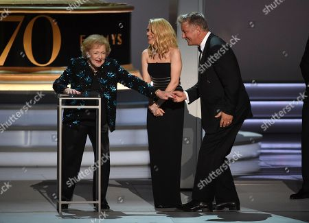 Betty White, Kate McKinnon, Alec Baldwin. Betty White, from left, Kate McKinnon and Alec Baldwin speak on stage at the 70th Primetime Emmy Awards, at the Microsoft Theater in Los Angeles