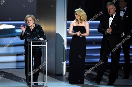 Stock Image of Betty White, Alec Baldwin, Kate McKinnon. Betty White, left, speaks at the 70th Primetime Emmy Awards, at the Microsoft Theater in Los Angeles. Looking on from right are Alec Baldwin and Kate McKinnon