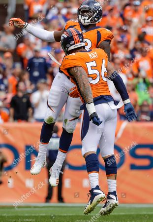 Denver Broncos linebacker Shaquil Barrett (48) celebrates a sack of Seattle Seahawks quarterback Russell Wilson (3) with teammate Shane Ray (56) during the first half of an NFL football game, in Denver