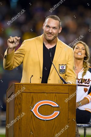 Chicago, Illinois, U.S. - Former Bear Linebacker Brian Urlacher speaks at the celebration of his Hall of Fame Induction with his wife in attendance during halftime at the NFL Game between the Seattle Seahawks and Chicago Bears at Soldier Field in Chicago, IL. Photographer: Mike Wulf