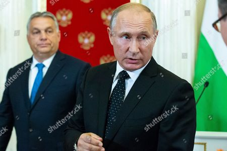 """Russian President Vladimir Putin, right, takes part in a joint news conference with Hungarian Prime Minister Viktor Orban, left, after their talks in the Kremlin in Moscow, Russia, . Putin says """"a chain of tragic circumstances"""" is to be blamed for a Russian military aircraft shot down by a Syrian missile. He vowed to boost security for Russian troops there"""