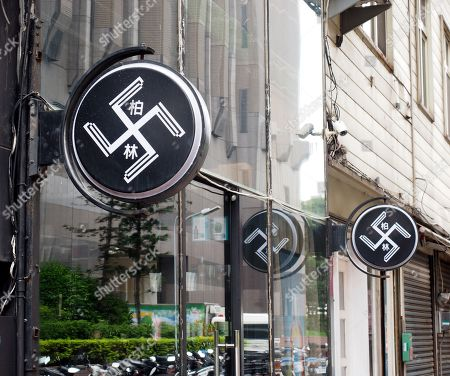 Two signs resembling a swastika plus the Chinese words 'Berlin' hang outside Berlin Hair Salon in Hsinchu City, northern Taiwan, 18 September 2018. The two signs have been there since the salon opened three years ago but caused controversy only recently when some foreigners alerted the German Institute in Taipei which demanded the salon remove the signs because they can be considered an offence against Holocaust victims. Salon owner Hsu Chen-yang said the logo was made by a design firm to show four blades and have nothing to do with swastika symbol that became infamous by the Nazi's usage of it, but he later said he would remove the signs if he could find the money. In recent years a dozen incidents involving Nazi symbol have occurred in Taiwan, including a restaurant selling 'Long Live Nazi' spaghetti and a high school turning its Christmas celebration into a Nazi parade with students waving Nazi flags and shouting 'Heil Hitler' to the school principal.