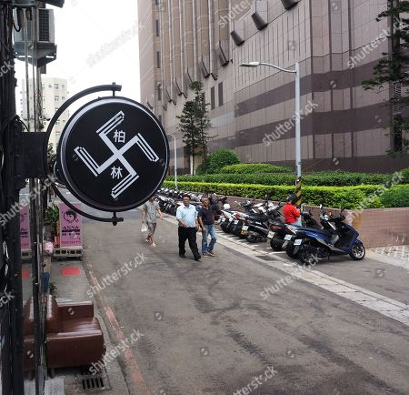 A sign resembling a swastika plus the Chinese words 'Berlin' hang outside Berlin Hair Salon in Hsinchu City, northern Taiwan, 18 September 2018. The two signs have been there since the salon opened three years ago but caused controversy only recently when some foreigners alerted the German Institute in Taipei which demanded the salon remove the signs because they can be considered an offence against Holocaust victims. Salon owner Hsu Chen-yang said the logo was made by a design firm to show four blades and have nothing to do with swastika symbol that became infamous by the Nazi's usage of it, but he later said he would remove the signs if he could find the money. In recent years a dozen incidents involving Nazi symbol have occurred in Taiwan, including a restaurant selling 'Long Live Nazi' spaghetti and a high school turning its Christmas celebration into a Nazi parade with students waving Nazi flags and shouting 'Heil Hitler' to the school principal.