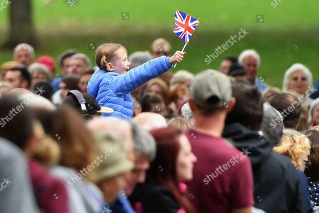 Stock Photo of A young girl waves a Union flag as Prince William arrives to unveil a new sculpture of Major Foley by artist Andy de Comyn.