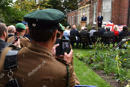 A member of the armed forces takes a photograph as Prince William listens to a speech by Ian Austin MP before unveiling a new sculpture of Major Frank Foley by artist Andy de Comyn. Major Foley was a British Intelligence Officer for the Embassy in Berlin where he bent the rules to allow thousands of Jewish families escape Nazi Germany
