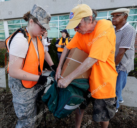 Stock Photo of A member of the Civil Air Patrol helps Jack Thompson, right, with a carton of MREs (Meals Ready To Eat) water and tarps at distribution area in Wilmington, N.C