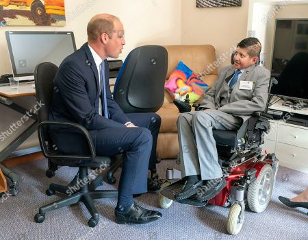 Britain's Prince William, left, meets Acorns Ambassador Coin Yours during his visit to Acorns Children's Hospice in Selly Oak, Birmingham, England, . The hospice provides specialist care for life limited and life threatened children and their families and was opened almost 30 years ago by Diana, Princess of Wales