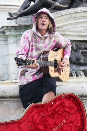 Stock Picture of Justin Bieber busking outside for Hailey outside Buckingham Palace