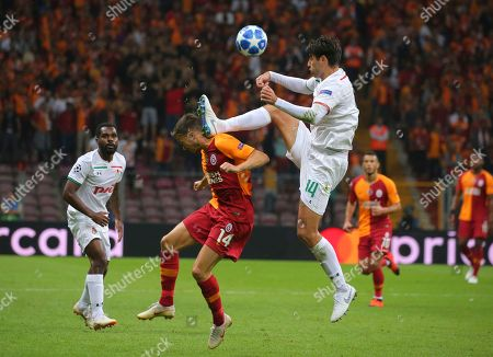 Galatasaray's Martin Linnes, left, tries to stop Lokomotiv Moscow's defender Vedran Corluka, right, during the Champions League Group D soccer match between Galatasaray and Lokomotiv Moscow in Istanbul