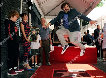Stock Image of Jack Black leaps over his new star on the Hollywood Walk of Fame, following a ceremony in Los Angeles. Looking on from left are Black's son Sammy, his wife Tanya Haden and his father Tom Black