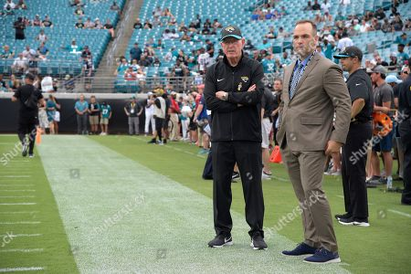 Jacksonville Jaguars general manager David Caldwell, right, and executive vice president of football operations Tom Coughlin watch warmups from the sideline before an NFL football game against the New England Patriots, in Jacksonville, Fla
