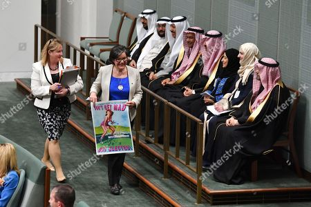 """Centre Alliance member for Mayo Rebekha Sharkie (L) and Independent Member for Indi Cathy McGowan (2-L) holding a poster saying """"Don't Get Mad, Get Elected"""" walk past a delegation from Saudi Arabia during House of Representatives Question Time at Parliament House in Canberra, Australia, 19 September 2018."""