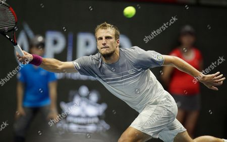 Mirza Basic of Bosnia and Herzegovina returns the ball to Mikhail Youzhny of Russia during the St. Petersburg Open ATP tennis tournament match in St.Petersburg, Russia