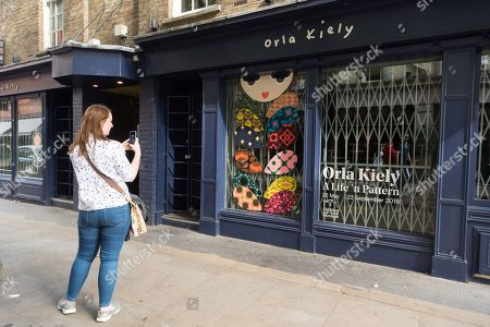 A woman wearing an Orla Kiely bag take a photo outside of a closed Covent Garden store as Orla Kiely £8 million retail empire collapses. It was reported the company ceased trading earlier this week with immediate job losses and unpaid staff wages.