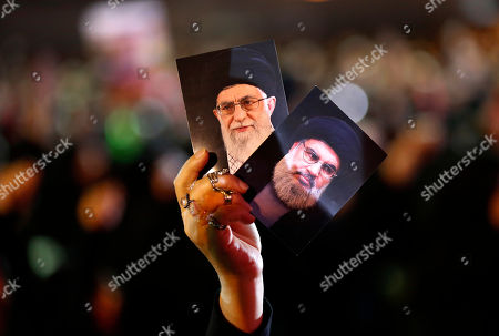 A Hezbollah supporter holds up portraits of Hezbollah leader Sheikh Hassan Nasrallah, right, and Iran's supreme leader Ayatollah Ali Khamenei, left, during activities to mark the ninth of Ashura, a 10-day ritual commemorating the death of Imam Hussein, in a southern suburb of Beirut, Lebanon, . Hassan Nasrallah says his group may reduce the number of its fighters in Syria because of an easing of the conflict, particularly after a recent Russian-Turkey agreement that prevented an offensive on the last rebel stronghold