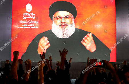 Hezbollah leader Sheik Hassan Nasrallah speaks via a video link, as his supporters raise their hands, during activities to mark the ninth of Ashura, a 10-day ritual commemorating the death of Imam Hussein, in a southern suburb of Beirut, Lebanon, . Hassan Nasrallah says his group may reduce the number of its fighters in Syria because of an easing of the conflict, particularly after a recent Russian-Turkey agreement that prevented an offensive on the last rebel stronghold