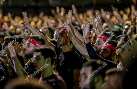 Supporters of Hezbollah raise their hands to salute Al-Hussein, as they listen to Hezbollah Secretary General Sayyed Hassan Nasrallah delivers a speech via a video link, during the night of the tenth of Muharram, the last night of 'Ashura' in the southern suburb of Beirut, Lebanon, 19 September 2018. Hassan Nasrallah addressed a number of political issues in Lebanon and the Arabic countries. Shiite Muslims across the world are observing Muharram, the first month of the Islamic calendar. The climax of Muharram is the Ashura festival commemorating the martyrdom of Imam Hussein, a grandson of the Prophet Mohammed in the Iraqi city of Karbala in the seventh century.