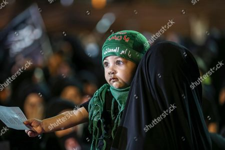 Stock Image of A supporters of Hezbollah carries a child as she listens to Hezbollah Secretary General Sayyed Hassan Nasrallah delivers a speech via a video link, during the night of the tenth of Muharram, the last night of 'Ashura' in the southern suburb of Beirut, Lebanon, 19 September 2018. Hassan Nasrallah addressed a number of political issues in Lebanon and the Arabic countries. Shiite Muslims across the world are observing Muharram, the first month of the Islamic calendar. The climax of Muharram is the Ashura festival commemorating the martyrdom of Imam Hussein, a grandson of the Prophet Mohammed in the Iraqi city of Karbala in the seventh century.