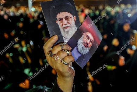 Stock Photo of A supporter of Hezbollah raises pictures of Hassan Nasrallah and Iran's Supreme leader Ayatollah Ali Khamenei, as they listen to Hezbollah Secretary General Sayyed Hassan Nasrallah delivers a speech via a video link, during the night of the tenth of Muharram, the last night of 'Ashura' in the southern suburb of Beirut, Lebanon, 19 September 2018. Hassan Nasrallah addressed a number of political issues in Lebanon and the Arabic countries. Shiite Muslims across the world are observing Muharram, the first month of the Islamic calendar. The climax of Muharram is the Ashura festival commemorating the martyrdom of Imam Hussein, a grandson of the Prophet Mohammed in the Iraqi city of Karbala in the seventh century.