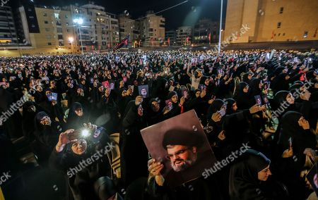 Stock Picture of Supporters of Hezbollah carry pictures of Hassan Nasrallah and Iran's Supreme leader Ayatollah Ali Khamenei, as they listen to Hezbollah Secretary General Sayyed Hassan Nasrallah delivers a speech via a video link, during the night of the tenth of Muharram, the last night of 'Ashura' in the southern suburb of Beirut, Lebanon, 19 September 2018. Hassan Nasrallah addressed a number of political issues in Lebanon and the Arabic countries. Shiite Muslims across the world are observing Muharram, the first month of the Islamic calendar. The climax of Muharram is the Ashura festival commemorating the martyrdom of Imam Hussein, a grandson of the Prophet Mohammed in the Iraqi city of Karbala in the seventh century.