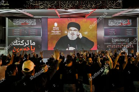 Supporters cheer as they watch Hezbollah Secretary General Sayyed Hassan Nasrallah (C) delivers a speech via a video link, during the night of the tenth of Muharram, the last night of 'Ashura' in the southern suburb of Beirut, Lebanon, 19 September 2018. Hassan Nasrallah addressed a number of political issues in Lebanon and the Arabic countries. Shiite Muslims across the world are observing Muharram, the first month of the Islamic calendar. The climax of Muharram is the Ashura festival commemorating the martyrdom of Imam Hussein, a grandson of the Prophet Mohammed in the Iraqi city of Karbala in the seventh century.