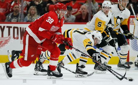 Pittsburgh Penguins center Adam Johnson (47) tries to steal the puck from Detroit Red Wings right wing Anthony Mantha (39) during the third period of an NHL preseason hockey game, in Detroit. The Red Wings defeated the Penguins 3-2
