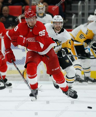 Detroit Red Wings right wing Anthony Mantha (39) is pursued down the ice by Pittsburgh Penguins center Adam Johnson, right, during the third period of an NHL hockey game, in Detroit