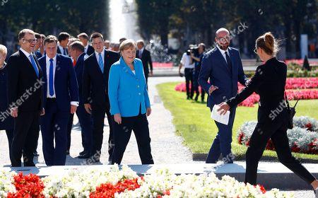 A staff member directs, from right, Belgian Prime Minister Charles Michel, German Chancellor Angela Merkel, Estonian Prime Minister Juri Ratas, Latvian Prime Minister Maris Kucinskis and Finnish Prime Minister Juha Sipila for family photo at the informal EU summit in Salzburg, Austria