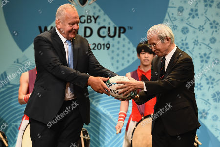(L-R)  Chairman of the World Rugby Bill Beaumont passes the ball to Chairman of the Japan Rugby Football Union Tadashi Okamura on stage during the Rugby World Cup One Year To Go event