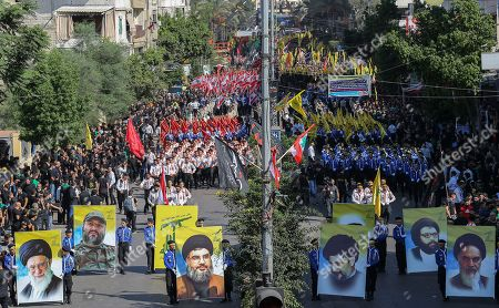 Hezbollah supporters carry pictures of pictures of Hezbollah leader Hassan Nasrallah and Iran's Supreme leader Ayatollah Ali Khamenei, Imad Mughnyeh, Imam Mussa Al- Sader and Iran's Supreme late leader Ayatollah Khumenei along their party flags with Islamic flags shout slogans as they march during Ashura Day procession in southern suburb of Beirut, Lebanon, 20 September 2018. Shiite Muslims across the world are observing Muharram, the first month of the Islamic calendar. The climax of Muharram is the Ashura festival commemorating the martyrdom of Imam Hussein, a grandson of the Prophet Mohammed in the Iraqi city of Karbala in the seventh century.